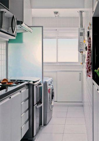 Sob a janela, o vão até o tanque foi aproveitado por um armário, que guarda tábua de passar, produtos de limpeza, varal de chão e aspirador de pó. Os armários aéreos e os gabinetes da cozinha foram planejados para acolher muitos utensílios e emoldurar a geladeira e o micro-ondas.