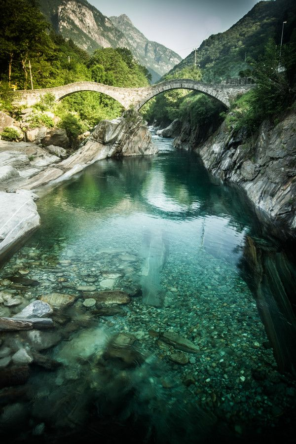 Walk the Ponte dei Salti bridge in the Valle Verzasca of Ticino, Switzerland.