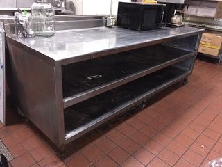 RESTAURANT EQUIPMENT STAINLESS STEEL WORKSTATION WITH STORAGE SPACE. CONTENTS NOT INCLUDED. 38H X 96W X 30D