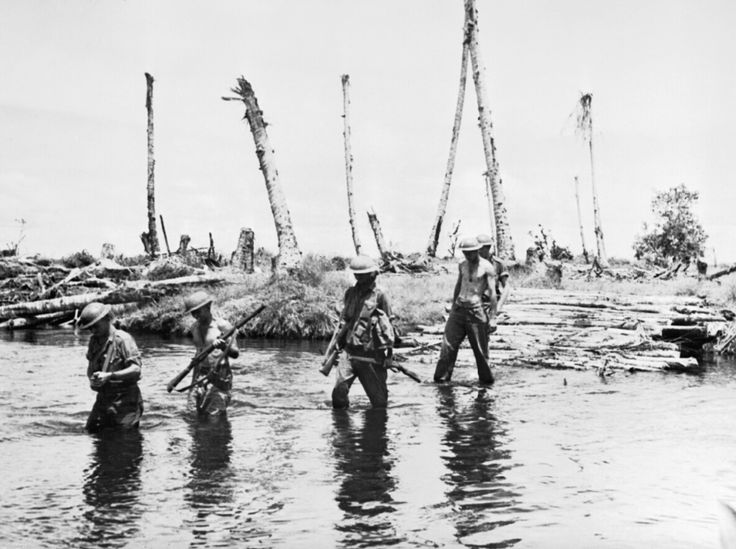 Australian soldiers wading through the waters along the coast of New Guinea towards Sanananda (1943)
