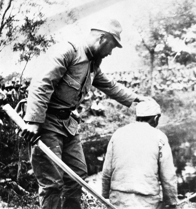 A Japanese headsman tells a Chinese prisoner how to hold his head for a quick decapitation during the Nanking Massacre, China, 1938