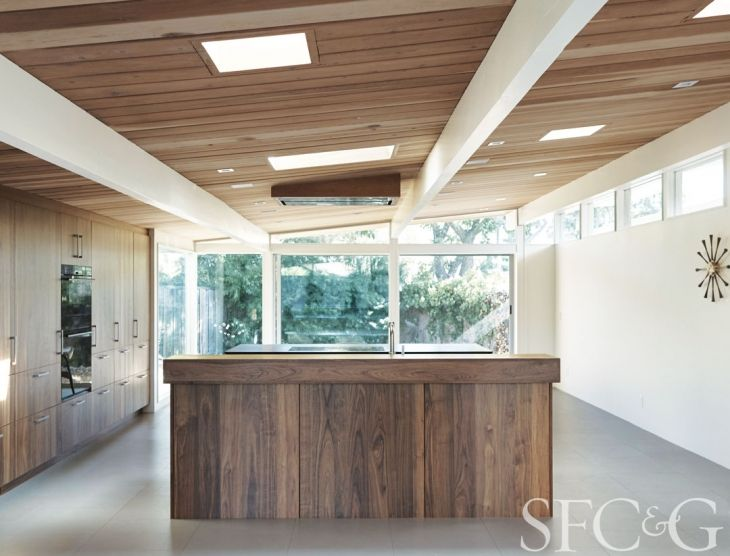 The prep island is equipped with Henrybuilt's Bar Block, where the owners gather and which stores frequently used items. The cooktop island has an induction range and additional storage for pots and pans. And a large oval Knoll table defines the dining space, which looks out upon the landscape. The room's plank-matched walnut cabinetry is a nod to the neighboring trees. The oven, steam oven and cooktop are Wolf; refrigerator is Sub-Zero; the sink is Elkay; faucet is Dornbracht.