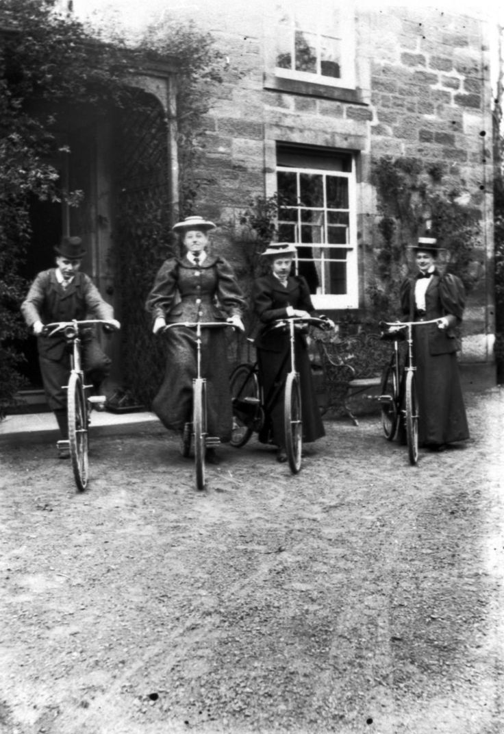 Four young riders posing with their bicycles outside the front door of Mount Esk, near Bonnyrigg, around 1895