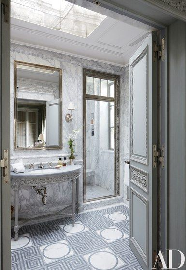 In the master bath, hand-carved details distinguish a custom-made vanity; the sink fittings and door hardware are by P. E. Guerin, and the marble-mosaic floor tile is by Smith for Ann Sacks   archdigest.com
