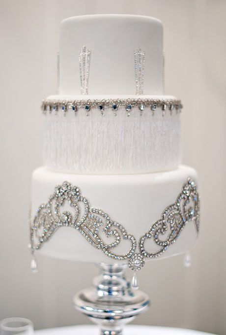Brides.com: . Vintage rhinestone appliqués and trim from the bride's collection of flea market treasures were added to the fondant-covered cake to complement the wedding's glamorous Art Deco theme.  Cake by The Butter End Cakery