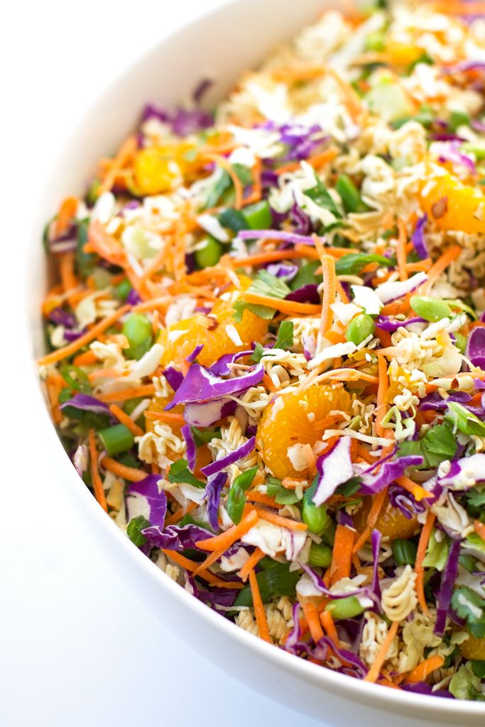Asian ramen noodle salads are a classic at potlucks! With fresh cabbage mix, shredded carrots, scallions, mandarin oranges, almonds, and sesame dressing.
