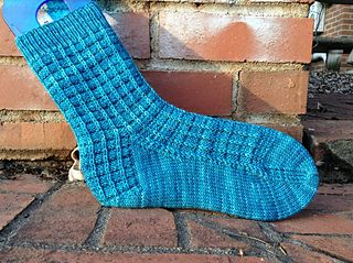 A companion to Spencer's Chessboard Scarf, slipped and textured stitches come together to create a block pattern reminiscent of a chessboard that wraps around the leg and continues uninterrupted through the heel. Knit these socks for yourself or your own Dr. Reid and take your game with you wherever you go!