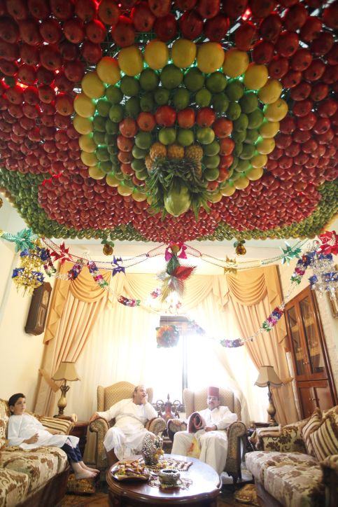 Samaritans sit in their living room with a home-made 'sukkah,' made from fresh fruit for the holiday of Tabernacles, or Sukkot, in Mount Gerizim near the West Bank town of Nablus on October 11, 2011. (Miriam Alster/ FLASH90)