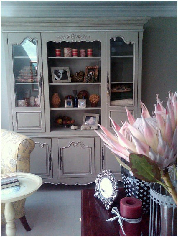 Grey green cabinet in the living space to use as storage and display