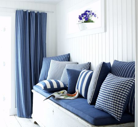 Prestigious Textiles -  Maritime Fabric Collection - Blue curtain with narrow white stripes, a plain blue bench seating pad with various blue and white striped and plaid cushions