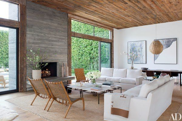 In the living room, a fireplace surround made of board-formed concrete anchors the space, while reclaimed-oak beams frame the glass walls and salvaged-pine siding lines the ceiling; the pendant lamp is by Treasurbite Design, the artworks are by Alison Van Pelt, and the throw is by Hermès.