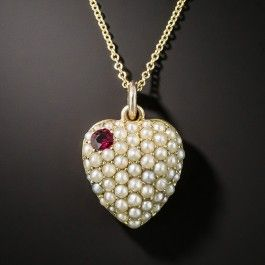 For Catholics and bleeding heart liberals alike, this puffed Sacred Heart pendant locket is studded with small lustrous seed pearls pierced in the upper left corner with a small gemmy red ruby. The reverse is outfitted with an open display locket. 15ct rose gold (hence of British origin). Consummate Victoriana, circa 1875. 13/16 by 9/16.