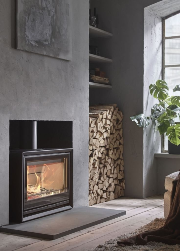 Interieur met houtkachel op vloerhoogte en houtopslag in de nis - Contura 330