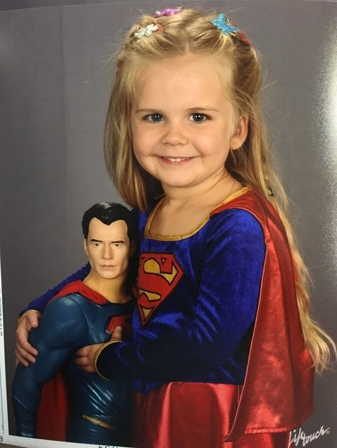 The result? This truly epic portrait, complete with adorable hair clips and a dashingly handsome Superman doll she's clutching ever so lovingly. | This 3-Year-Old Picked Her Own Outfit For School Photos, And It's Epic