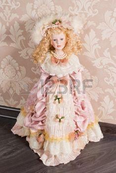 antieke+pop%3A+Mooie+delicate+antieke+pop+met+lange+blonde+krullen%2C+gekleed+in+een+mooie+roze+negentiende-eeuwse+jurk+en+accessoires+Stockfoto