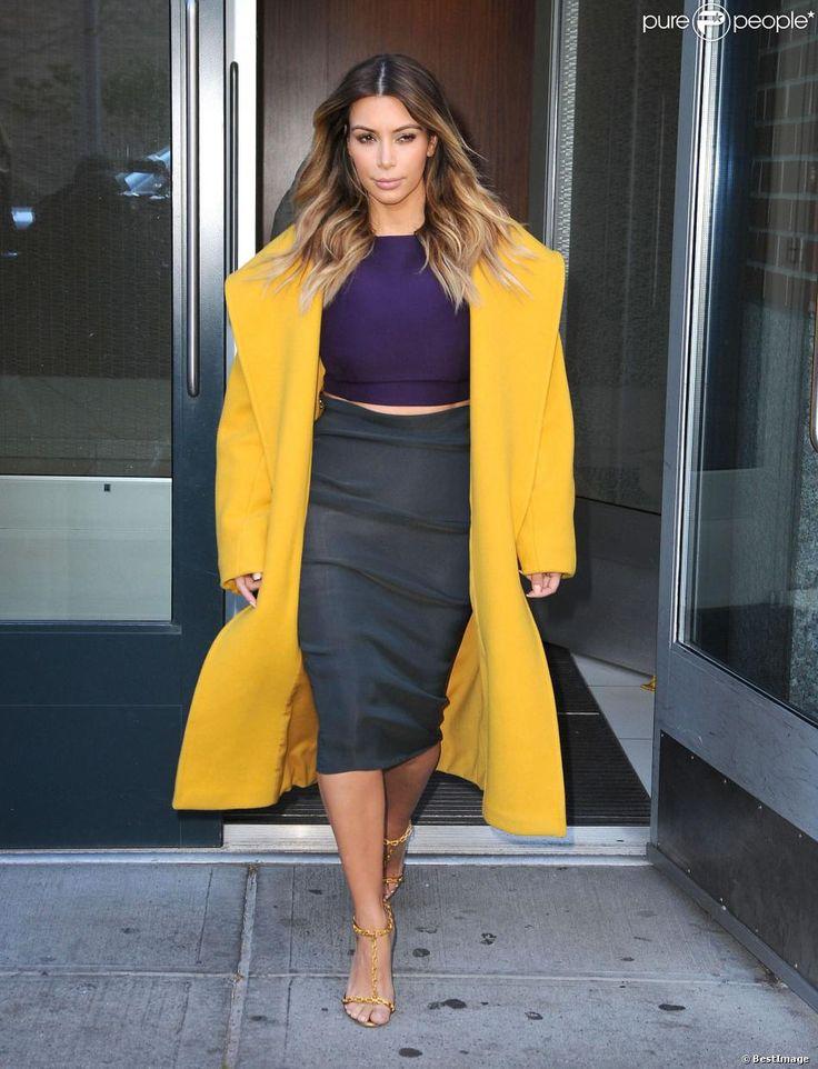 Kim Kardashian, lumineuse dans un manteau jaune Max Mara porté avec un crop top violet, une jupe Lanvin et des sandales Tom Ford. SoHo. New York, 20 novembre 2013.