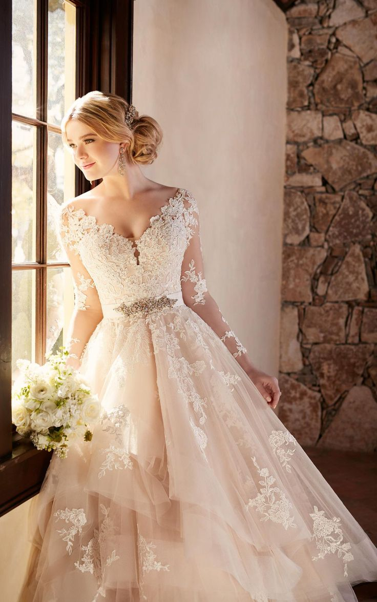 """This elegantly crafted designer tulle wedding dress from Essense of Australia features alluring illusion lace sleeves and eye-catching cuts of tulle on its skirt. Choose from silver or gold Diamante embellishments. A 1.5"""" beaded grosgrain belt slims the waist. The back zips up under sparkling crystal buttons."""