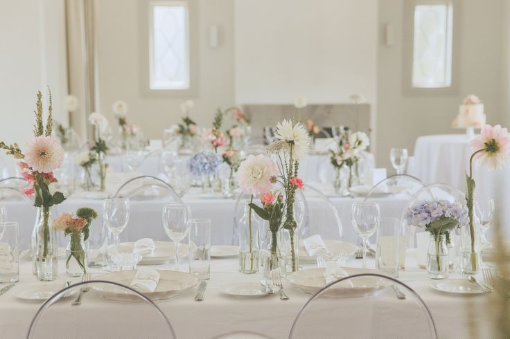 long tables with collection of antique bottles filled with fresh summer blooms in vintage tones