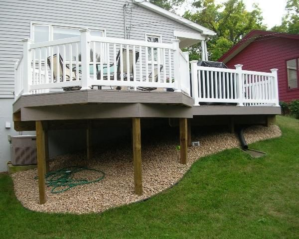 Level Deck For A Hilly Yard I Also Like The Rocks Gravel Under The Deck So They Didn T Have To Worry Ab Deck Landscaping Under Deck Landscaping Decks Backyard