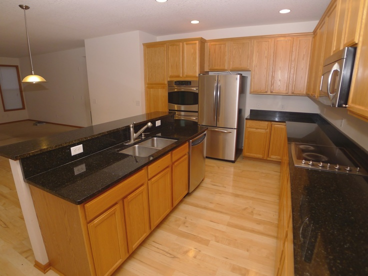 Fabulous Open Kitchen With Black Granite Countertops And