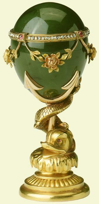 This Fabergé seal was kept on King George V's desk at Buckingham Palace and was likely purchased on 28 October 1912 for £19. It consists of a handle of polished nephrite with red and yellow gold, diamond and ruby mounts in the form of a band, from which swags of leaves centred by a rose are suspended. The handle is mounted on a base of red and yellow gold in the form of an entwined dolphin. The gold matrix is engraved with the crowned cipher of the King. Michael Perchin, c. 1900.