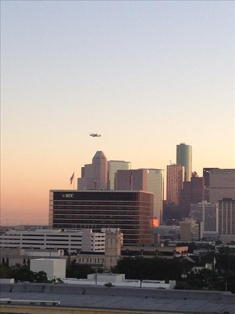 Shuttle Endeavour flying over Downtown Houston as seen from Midtown with Houston Community College in the foreground.