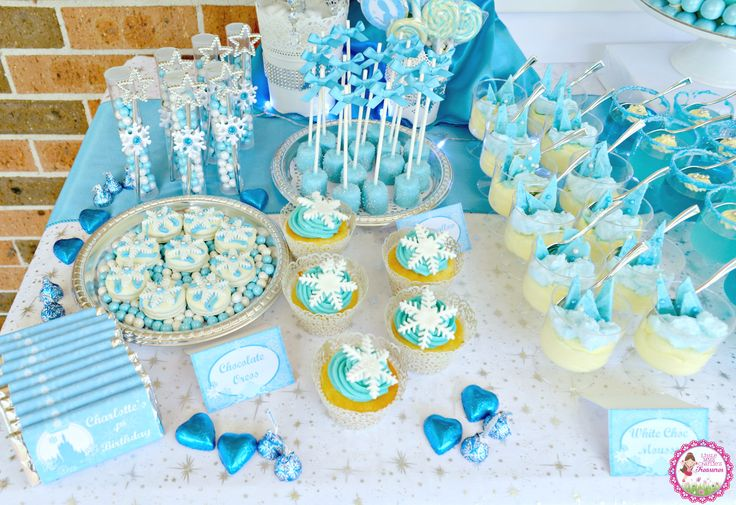 Frozen themed desserts and sweets - vanilla cupcakes with buttercream frosting and fondant snowflake, chocolate covered marshmallows and chocolate covered oreos with fondant snowflakes by Little Miss Charlie's Treasures