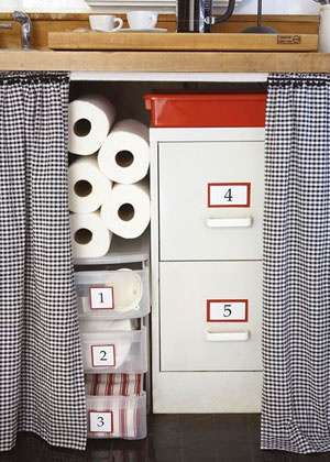 Storage Solutions UNDER-CABINET STORAGE Dress up an ordinary sink stand in no time by adding a cotton seersucker skirt. Plastic bins and a small file cabinet keep things tidy.