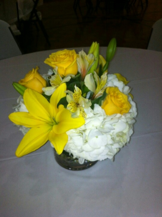 White hydrangeas, yellow roses, yellow alstroemeria blooms, and yellow lilies