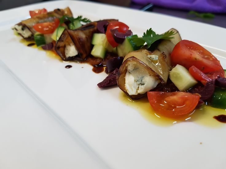 Char grilled aubergine filled with blue cheese and sun dried tomato topped with olive and cucumber salsa olive oil and balsamic dressing