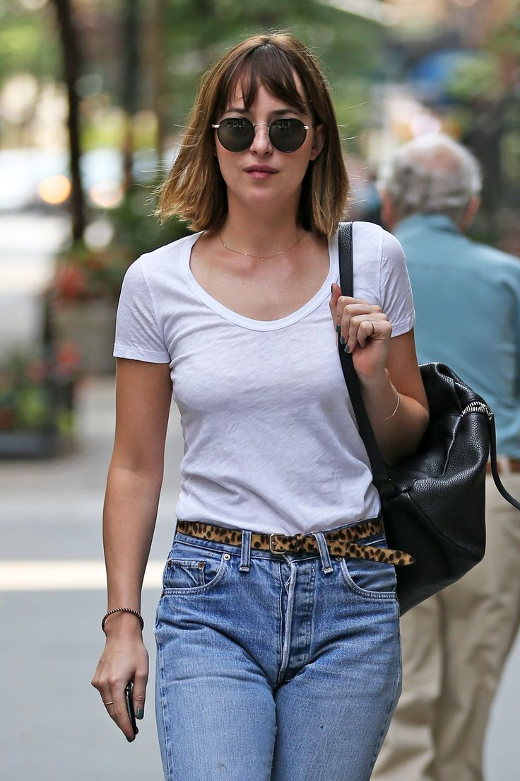 Dakota Johnson embraces a laid-back fresh beauty palette paired with a white tee, high waist vintage jeans and a black backpack with round sunglasses