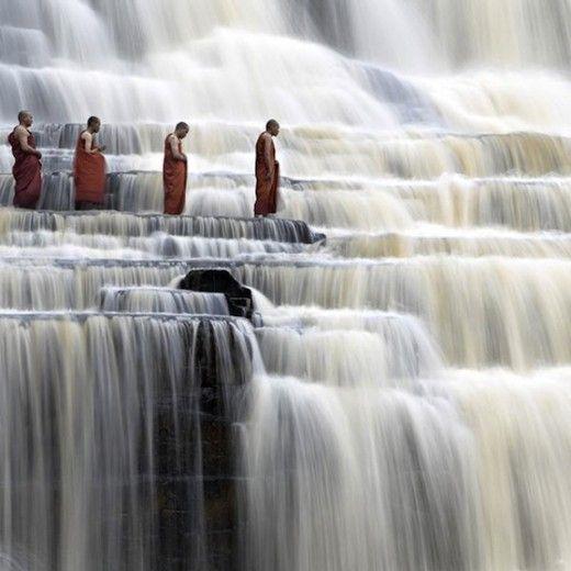 Monks walking through the Pongua falls in Vietnam