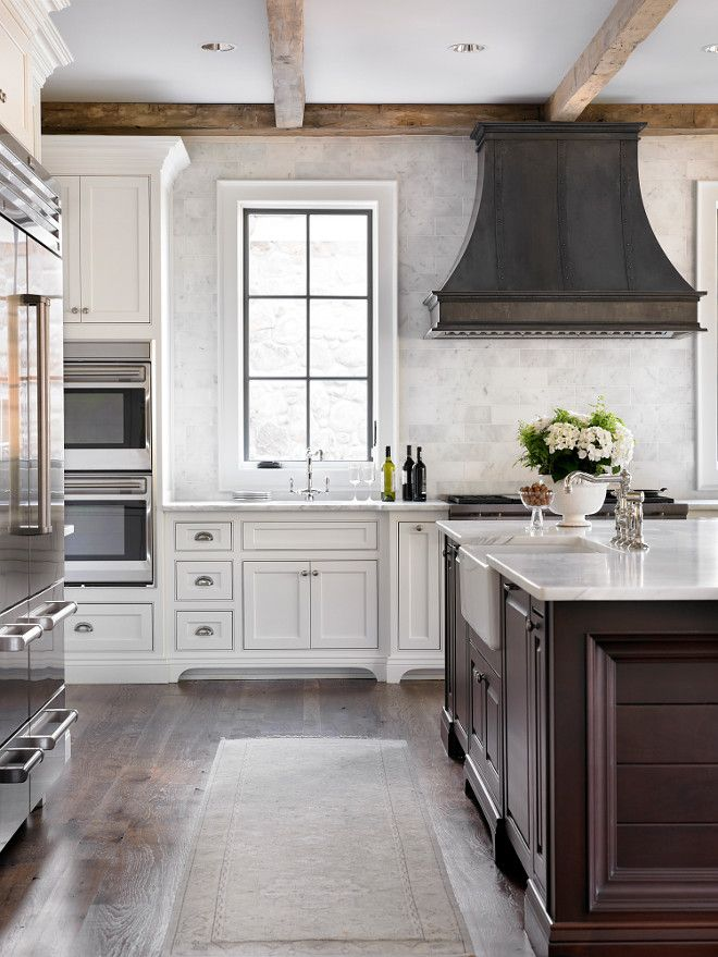 French Country kitchen with reclaimed wood beams and zinc French kitchen hood…