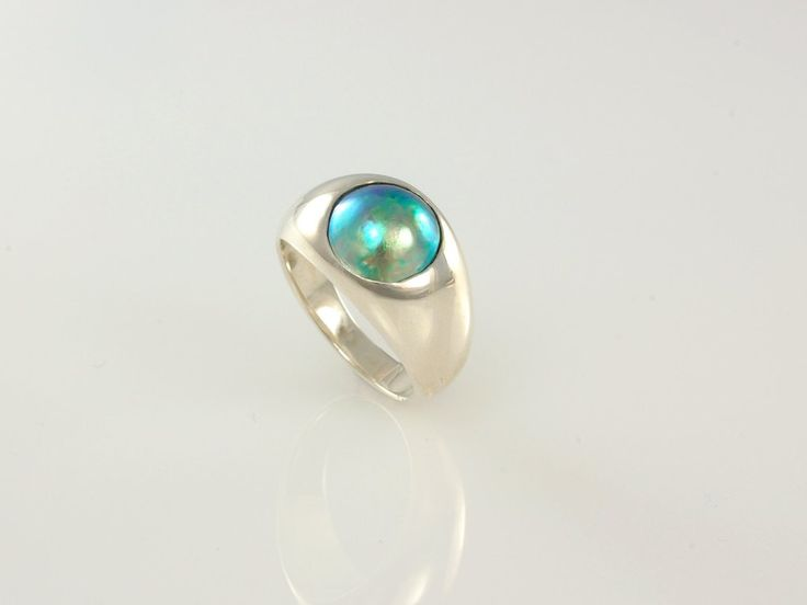 -Waikawa- NZ$849- Silver with New Zealand Blue Pearl. Simple but stylish domed ring design sets off the natural beauty and iridescence of the pacific blue pearl. The ring is wide but tapers at the back for comfort. If you would like this design in gold or another alloy, we'd be happy to make you one, just ask us for a quote! Ring width top 12mm tapering to 3.4mm, ring size O, 10mm B grade Pacific Blue Pearl, Eyris Pearls. Certificate included. Jewellery made @jewelbeetle in Nelson, New…