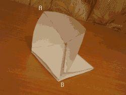 Ahora, observando la fotografía anterior, doblar el vertice C hacia el B por encima de la cara superior.  Obtendremos el resultado de la fotografía de la derecha:   A continuación doblar el último vertice A hacia las esquinas B.