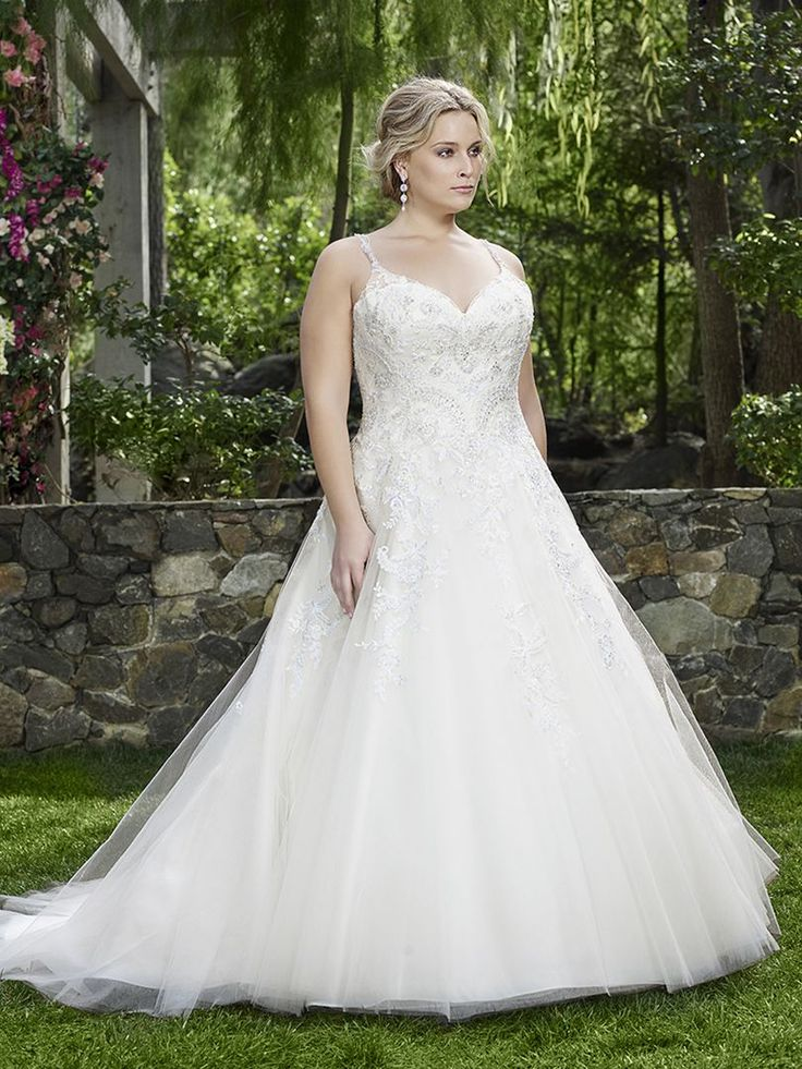 Style 2248 Juniper by Casablanca Bridal. Alencon lace over dreamy, silky satin adorns Juniper's bodice and cascades down onto the cathedral length train. Dainty beaded straps compliment the feminine v neckline. This ball gown promises to be as timeless and tender as the bride who wears it. #plussizeweddingdress #plussizebride