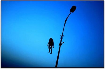 """""""uomo blu"""" - un uomo salta da un lampione sul fiume Tigri a Bagdad - foto di Ben Lowi"""