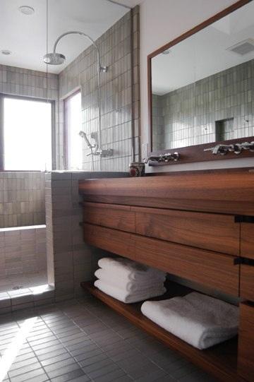 bathroom. shower fixtures. sink fixtures. wood cabinet. mirror.