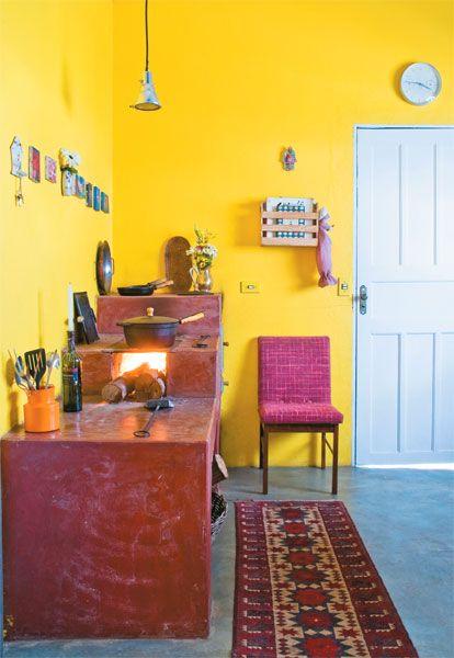 O fogão à lenha ajuda a aquecer a casa toda. O piso de cimento queimado é original da construção.