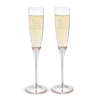 Bring a timeless trend to your wedding day with these personalized rose gold    wedding toasting flutes. A beautiful way to sip champagne on your wedding day,  these flutes feature rose gold detailing around the polished silver base of each flute. Engrave your names, wedding date and a meaningful quote or saying on     each glass to personalize your wedding day!<br><br>-Hand wash only<br>-Matching knife and cake server available<br>-A beautiful personalized wedding or         anniversary…