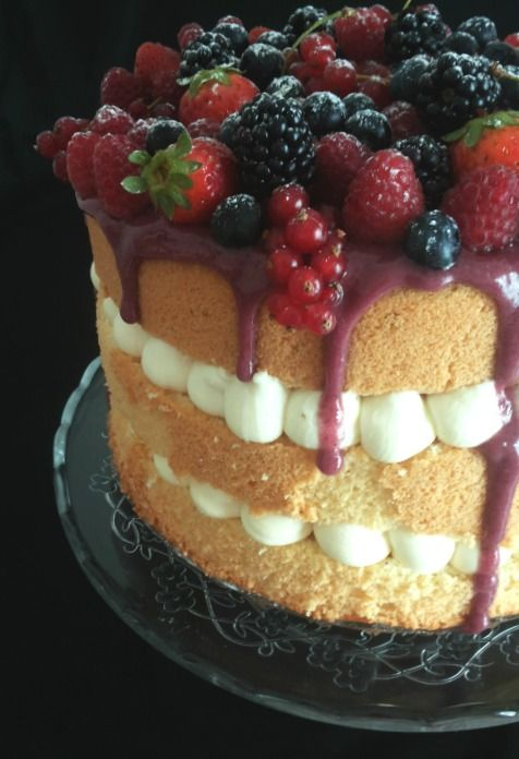 fluffosa alla vaniglia con namelaka al cioccolato bianco e una cascata di frutti di bosco su glassa al succo di mirtillo