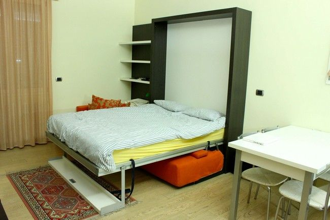 double bed vertical with orange sofa under it with eastern asian carpet on the floor