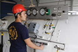 Student operates a hyperbaric chamber at the International Diving Institute (IDI).