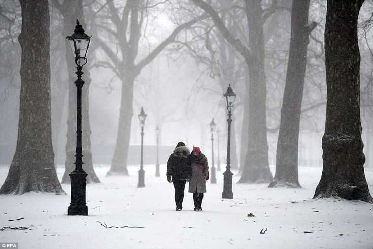 A couple walk hand-in-hand through Green Park today in London. Hospitals have cancelled op...