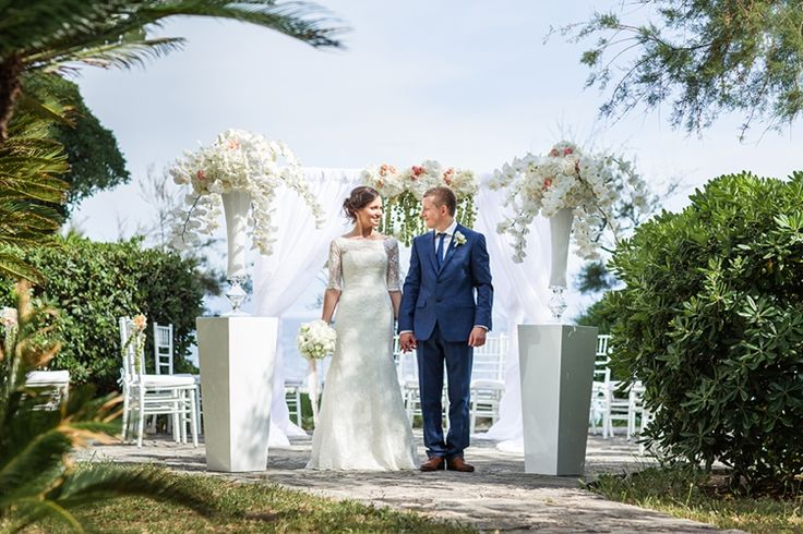 Sparkling Turquoise Waters: Croatia Destination Wedding | The happy newlyweds at the Lovely white arch with floral arrangements by Flower and Sweet Fairy. Wedding Planner: Adriatic Weddings Croatia. #Croatia #seawedding #destinationwedding #white