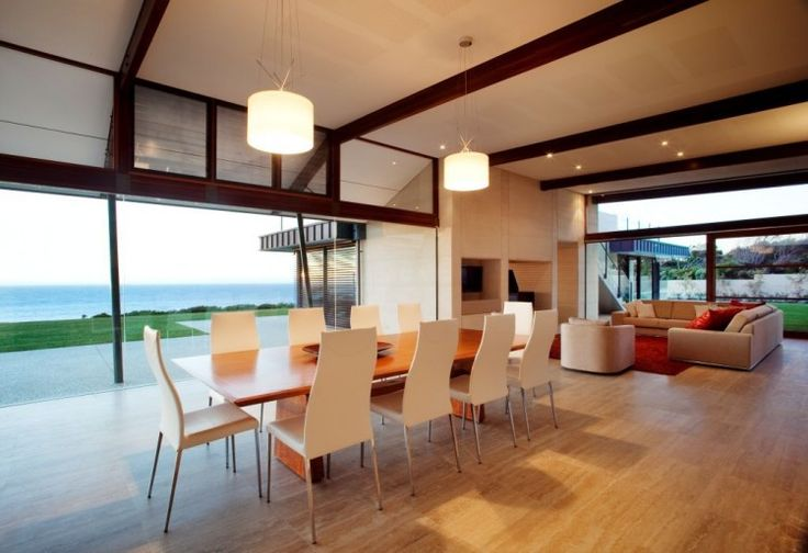 Stunning View From A Modern Minimalist House:dining-room-with-loong-wooden-table-ten-white-chair-chandelier-big-glass-wall-and-beach-landscape