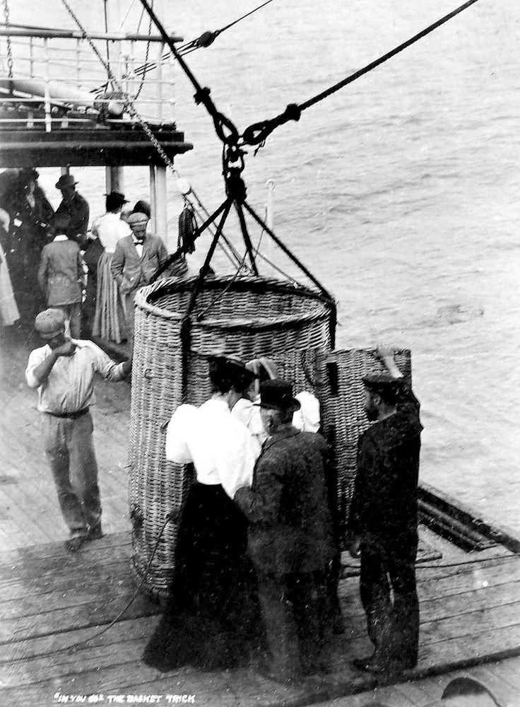 """Captioned: """"In You Go"""", The Basket Trick, the on board going of passengers unto awaiting ships in our main harbours around 1912. Hilton T"""