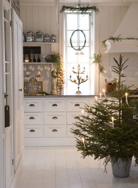 A Scandinavian Christmas - A tree in the middle of the room: not many kitchens can pull this off w/ style. The white painted wood floors, beadboard walls & country charm of this Swedish space are a perfect backdrop for fresh greenery & a tree minimally decorated w/ lit candles. (Look for the battery operated Everlasting candles if you ever plan to do this.)
