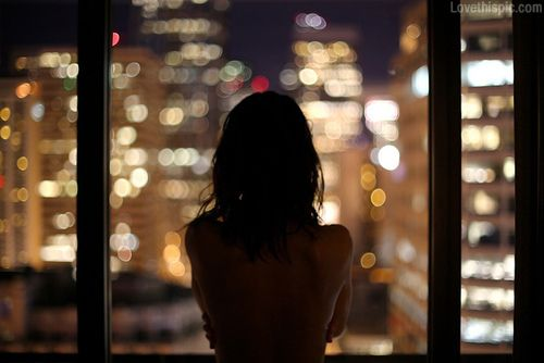 Looking out bokeh night lights girl lonely window
