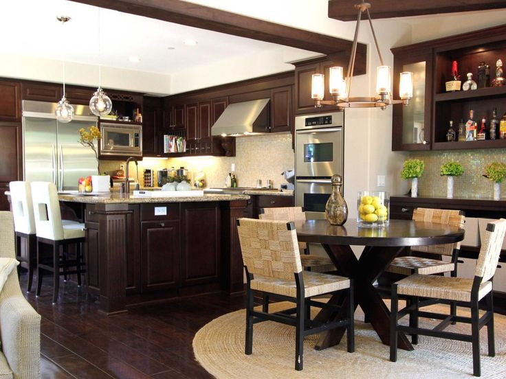 A Round Dining Room Table Is Flanked By Four Chairs And